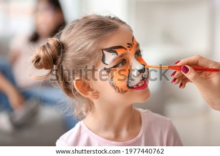 Woman painting face of little girl at home