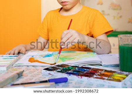 Caucasian kid painting on paper with paintbrush and water colors at table.