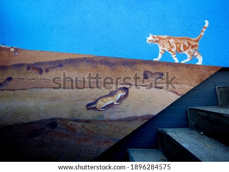 naturalistic painted red redhead cat walking over painted layers of earth with animals at a cellar staircase on the facade wall painting on a block of flats in Wuppertal, Germany