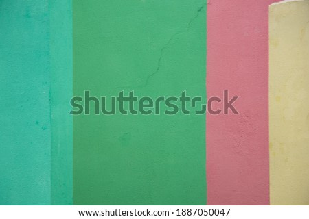 the wall of the house is painted in different colors yellow green purple as a background