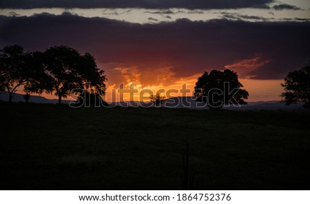 the sun setting and creating a very orange layer in the middle of mountains and hills