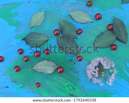 red ripe currants with green leaves on the glass decorated with watercolor.