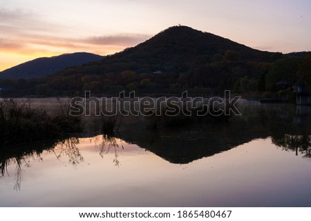 Calming view of Mountain with reflection on the water at the morning sunrise with purple sky in Incheon Grand Park, South Korea