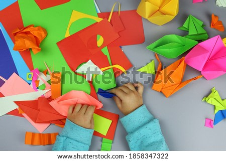 child makes origami crafts from colored paper