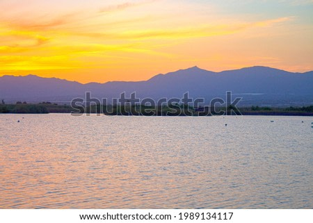 Watercolor sunset on the background of mountains and fields.