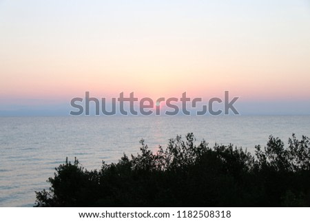 Amazing sunrise at Mediterranean sea in Greece. Colorful view at early summer morning sun trought coast trees.