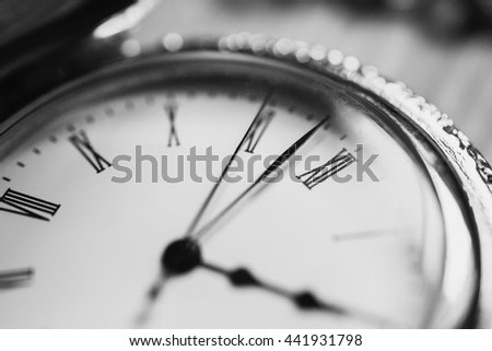 black and white art photography monochrome, open pocket watch and chain lie on a light wooden table background, arrow on the clock