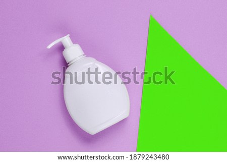 Bottle of liquid soap on colored paper background with geometric shapes. Shower gel, shampoo. Pop art style. Top view
