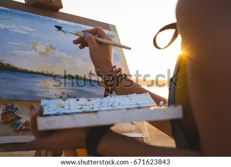 Young woman artist painting landscape in the open air on the beach, close up