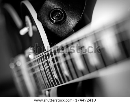 Macro abstract black and white photo of the neck and frets of an electric guitar.