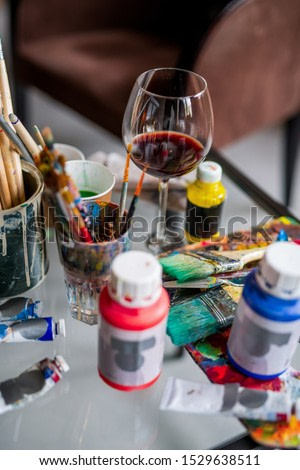 Glass of red wine among paintbrushes and various paints and gouaches on workplace of an artist