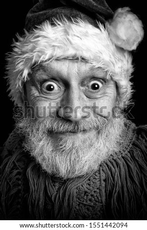 Black and white portrait of an adult man with white beard disguised in Santa Claus for the Christmas Holiday