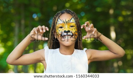 Little african-american girl with tiger face painting roaring, making funny grimace outdoors, copy space