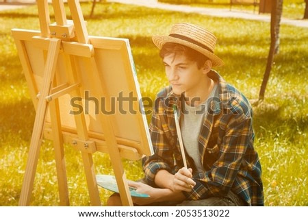 Autumn photo of the artist in the park. Photo in warm colors. Against the background of yellow foliage