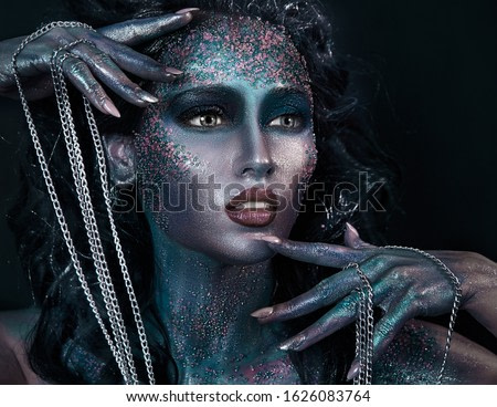 close up  portrait of young beautiful girl with colorful face painting. Halloween professional makeup. hair in paint. beauty portrait. colorful beads on face. chain in hands