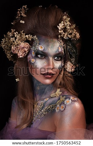 close up portrait of young beautiful girl with flower professional makeup. elf princess with flower crown on head.  Halloween makeup. bright blue face art. spring fairy of flowers