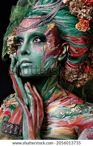close up portrait of young beautiful girl with flower professional makeup. elf princess with flower crown on head.  Halloween colorful makeup. bright face art. spring fairy of flowers