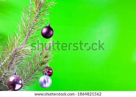 A Christmas toy hangs on a branch of a Christmas tree.
