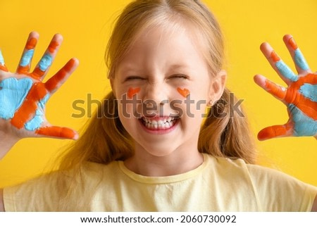 Little girl with in paint on yellow background, closeup
