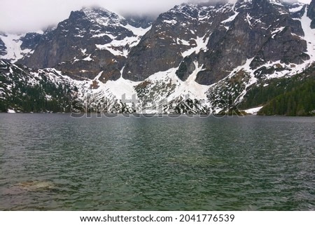 Beautiful mountain lake with dark water against the background of the mountain
