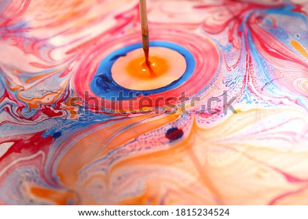 Beautiful ornament from the ink floated on water.A person draw it with wooden stroke.