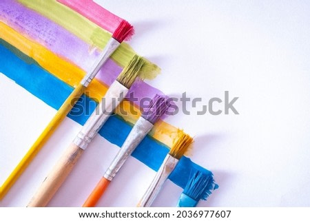 five brushes lie on a white canvas with colored lines drawn, close-up