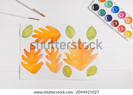 Step-by-step tutorial autumn paper wreath. Step 1: Paint autumn leaves of different shapes, sizes and colors with watercolors. Top view