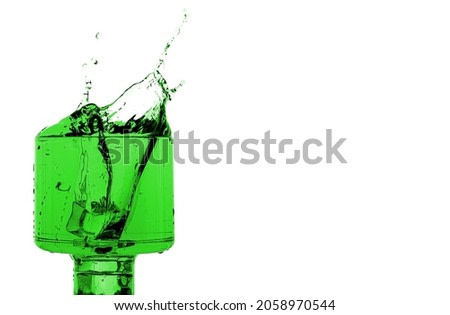 drink splashing creating an art shape with green light effects isolated on white background.