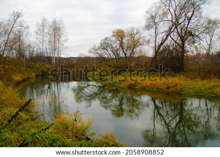 Autumn landscape on a gloomy foggy morning - with trees and bushes along the banks of the river and with reflections in the water.