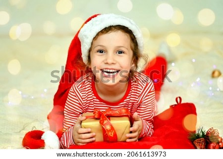 A little smiling girl in Santa's red hat and red christmas clothing lies on the bed with a gift. Preparation for the celebration. New Year. hildren's Christmas. Atmosphere. Home.