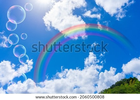 Background of rainbow and glittering bubbles over the blue sky