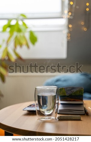 Glass cup of hot water on wooden table with watercolor drawing in paper notebook near home flower and bed in bedroom near window and lights on cozy cloudy autumn or winter day. Drink, weekend, holiday