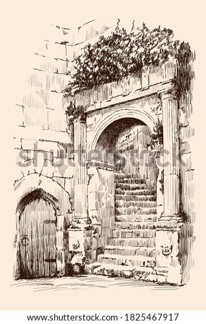 Fragment of an urban stone building with a spiral staircase, arch and door.